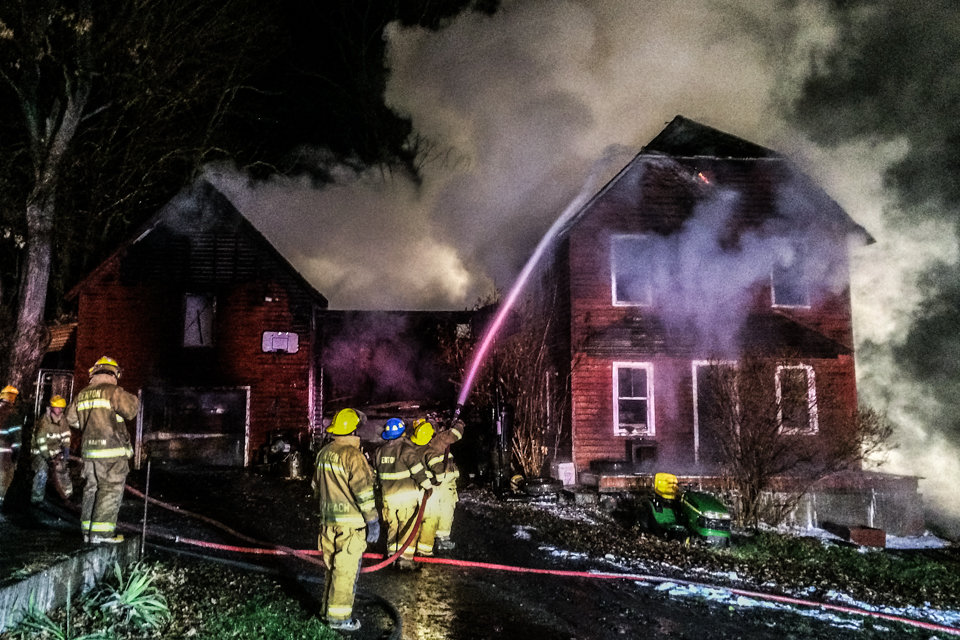 Image of firefighters putting water on barn fire.
