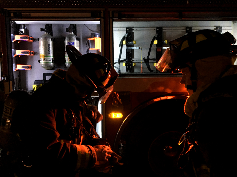 Image of firefighters putting on gear.